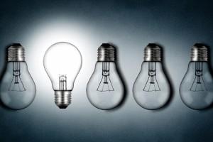 Illuminated lightbulb amid dim bulbs - creativity and innovation concept